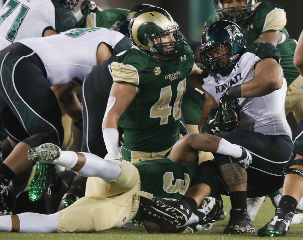 . Hawaii running back Joey Iosefa, right, is stopped after a short gain by Colorado State linebackers Cory James, bottom left, and Max Morgan in the first quarter of an NCAA college football game in Fort Collins, Colo., on Saturday, Nov. 8, 2014. (AP Photo/David Zalubowski)
