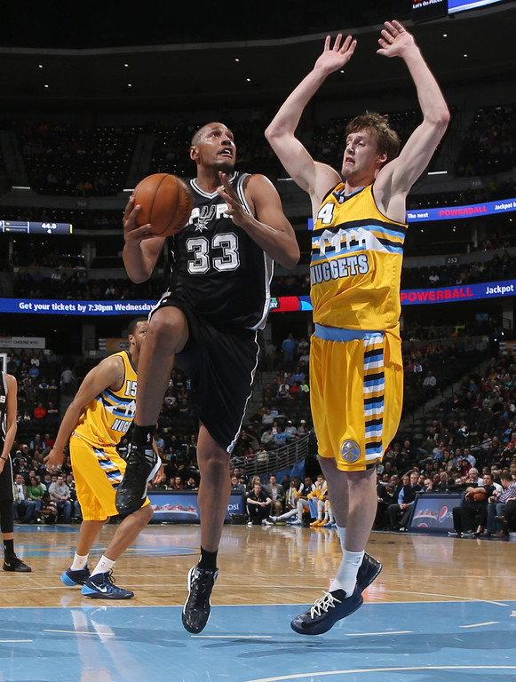 . San Antonio Spurs forward Boris Diaw, left, of France, drives the lane for shot as Denver Nuggets forward Jan Vesely, of the Czech Republic, defends during the fourth quarter of the Spurs\' 133-102 victory in an NBA basketball game in Denver on Friday, March 28, 2014. (AP Photo/David Zalubowski)