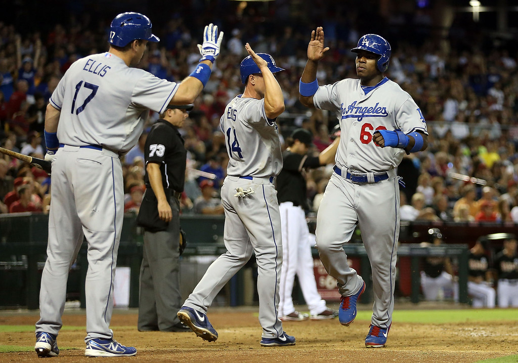 . PHOENIX, AZ - JULY 10:  Yasiel Puig #66 of the Los Angeles Dodgers high fives Mark Ellis #14 and A.J. Ellis #17 after scoring a run against the Arizona Diamondbacks during the fifth inning of the MLB game at Chase Field on July 10, 2013 in Phoenix, Arizona.  (Photo by Christian Petersen/Getty Images)