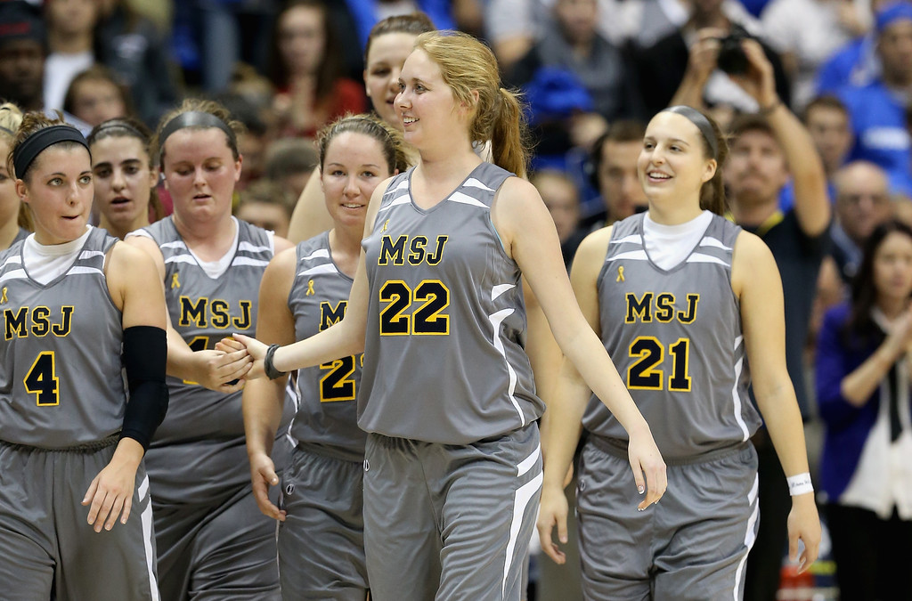 . Lauren Hill of Mount St. Joseph celebrates with her teammates after the game against Hiram at Cintas Center on November 2, 2014 in Cincinnati, Ohio. Hill, a freshman, has terminal cancer and this game was granted a special waiver by the NCAA to start the season early so she could play in a game.  (Photo by Andy Lyons/Getty Images)