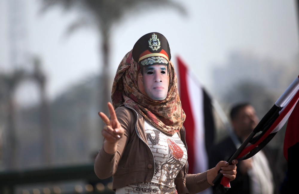 . An Egyptian woman wears a mask of Egypt\'s Defense Minister Gen. Abdel-Fattah el-Sissi in Tahrir Square, in Cairo, Egypt, Saturday, Jan. 25, 2014. Egyptian riot police have fired tear gas to disperse hundreds of supporters of ousted Islamist President Mohammed Morsi protesting as the country marks the third anniversary of the 2011 uprising, as supporters of the military gathered in rival rallies in other parts of the capital, many of them urging military chief El-Sissi, the man who removed Morsi, to run for president. (AP Photo/Khalil Hamra)