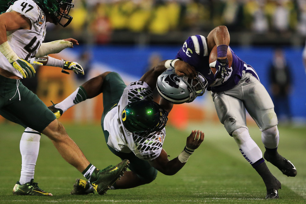 Description of . John Hubert #33 of the Kansas State Wildcats is tackled by Boseko Lokombo #25 of the Oregon Ducks during the Tostitos Fiesta Bowl at University of Phoenix Stadium on January 3, 2013 in Glendale, Arizona.  (Photo by Doug Pensinger/Getty Images)