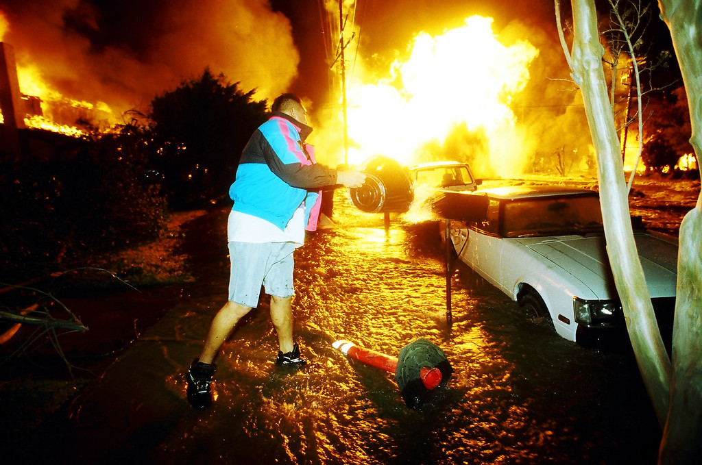 . Terrence Bito douses his car with water as flames approach on Balboa Boulevard.   Los Angeles Daily News file photo
