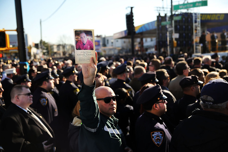 . A man holds up a picture of New York City Police Officer Rafael Ramos outside of the Christ Tabernacle Church during the funeral of Officer Rafael Ramos, one of two officers murdered while sitting in their patrol car in an ambush in Brooklyn last Saturday afternoon on December 27, 2014 in the Glenwood section of the Queens borough of New York City. Thousands of fellow officers, family, friends and Vice President Joseph Biden are expected at the church in the Glendale neighborhood of Queens for the funeral.  (Photo by Spencer Platt/Getty Images)