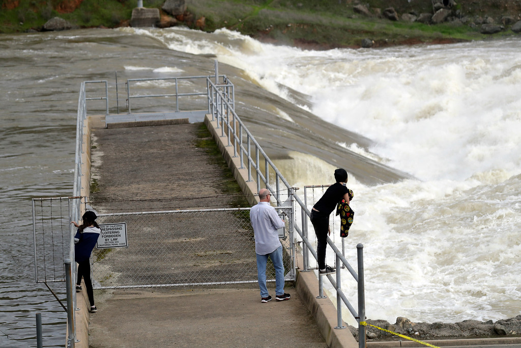 . People watch the gushing waters of the Feather River from the town\'s fish hatchery a day after an evacuation was lifted Wednesday, Feb. 15, 2017, in Oroville, Calif. Authorities say the immediate danger has passed and allowed people living downstream of the Oroville Dam to go back home Tuesday after ordering an evacuation Sunday. But new storms forecast to hit Northern California this week will test quick repairs to the dam.  (AP Photo/Marcio Jose Sanchez)
