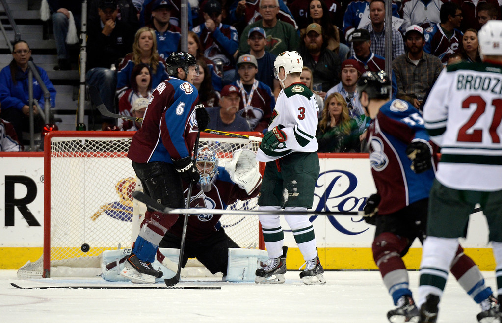 . DENVER, CO - APRIL 26: Minnesota Wild center Kyle Brodziak (21) shoots a puck that just gets past Colorado Avalanche defenseman Erik Johnson (6) and Colorado Avalanche goalie Semyon Varlamov (1) and lands in the Avalanche net during the third period of action. The Colorado Avalanche hosted the Minnesota Wild in the fifth round of the Stanley Cup Playoffs at the Pepsi Center in Denver, Colorado on Saturday, April 26, 2014. (Photo by John Leyba/The Denver Post)
