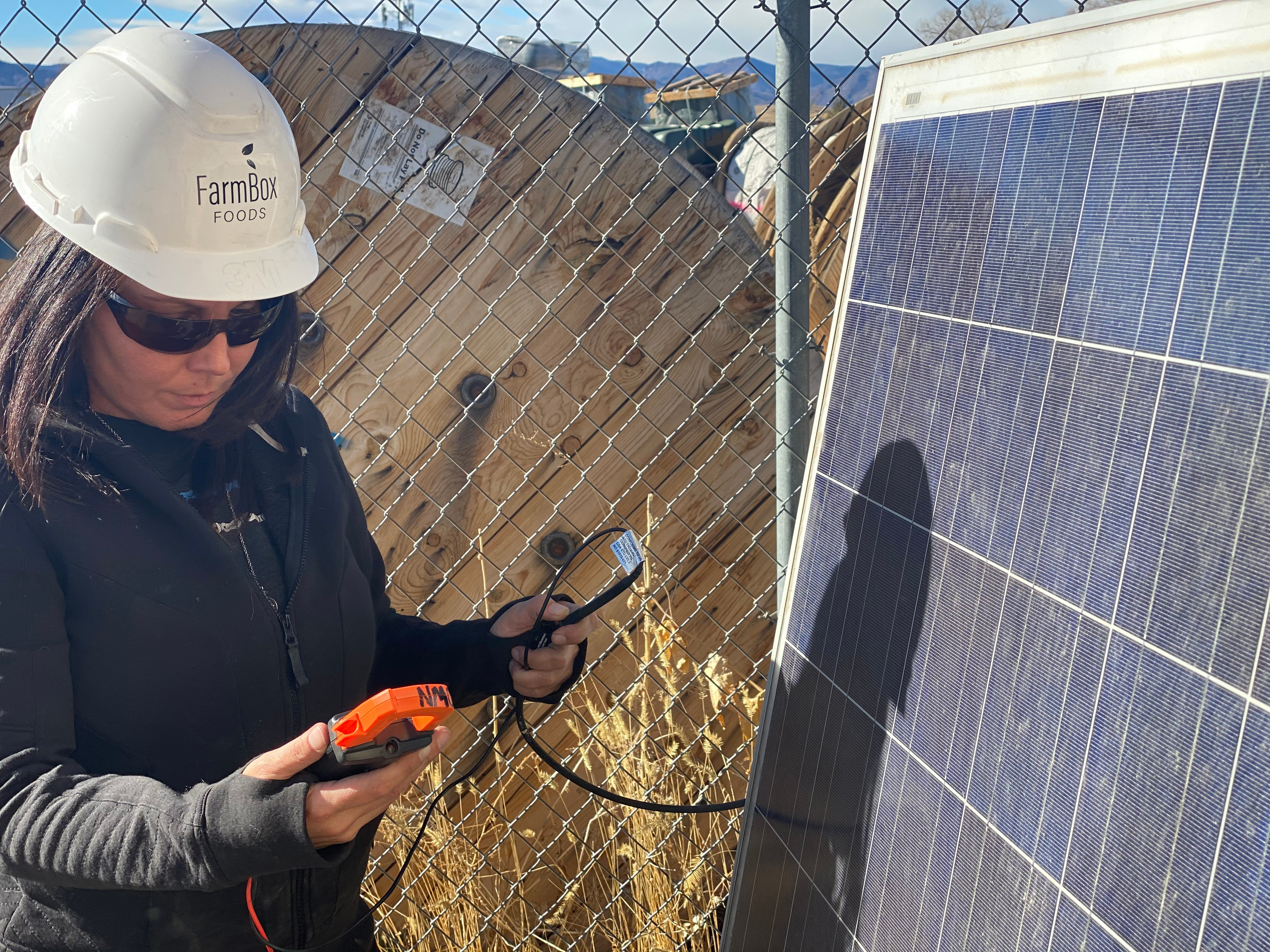 Adrienne Cloud tests the solar panel voltage output with a multimeter.
