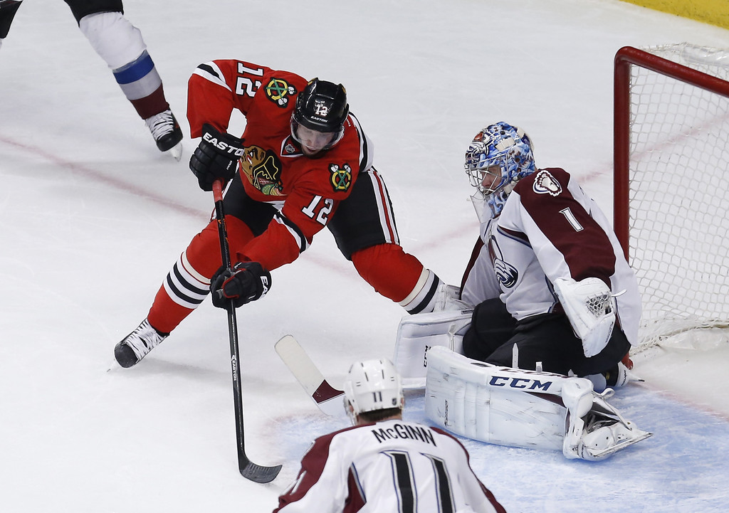 . Colorado Avalanche goalie Semyon Varlamov (1) makes a save on a shot by Chicago Blackhawks center Peter Regin (12) as Avalanche\'s  Jamie McGinn (11) watches during the second period of an NHL hockey game Tuesday, March 4, 2014, in Chicago. (AP Photo/Charles Rex Arbogast)