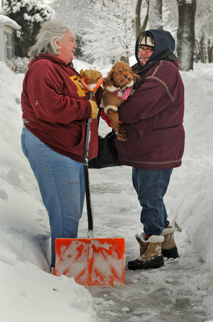 . Jane Gehr, left, takes a brief break from shoveling in St. Paul Friday to visit with Mary Jo Parker and her well-dressed Cockapoo.  Gehr is a veterinarian at Arcade Animal Hospital.  (Pioneer Press: Jean Pieri)