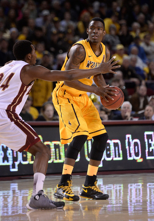 . Wyoming Cowboys forward Derek Cooke Jr. (11) looks to make a pass as Denver Pioneers forward Chris Udofia (34) defends on the plan during the first half December 15, 2013 Magness Arena. (Photo by John Leyba/The Denver Post)