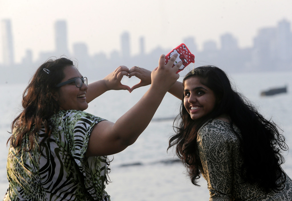 . Girls take a selfie sitting by the Arabian Sea promenade on Valentine\'s Day in Mumbai, India, Tuesday, Feb 14, 2017. (AP Photo/Rajanish Kakade)