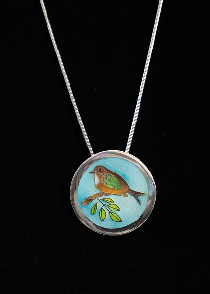 Fine Silver Champlevé and Cloisonné fantasy bird on leafy branch. Pendant measures 1 1/2 inches in diameter. Supported on a 16 inch Sterling silver chain. 185.00