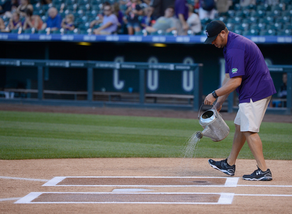. DENVER, CO. - AUGUST 16:  Colorado Rockies assistant grounds keeper, Jason Garner, use a watering can with ice water from the Cincinnati Reds dugout to water down home plate at Coors Field Saturday evening, August 16, 2014. The Rockies were set to play the Cincinnati Reds but the game was cancelled due to a water main break along Blake St, out in front of Coors Field, cutting off water supply to the stadium. (Photo By Andy Cross / The Denver Post)