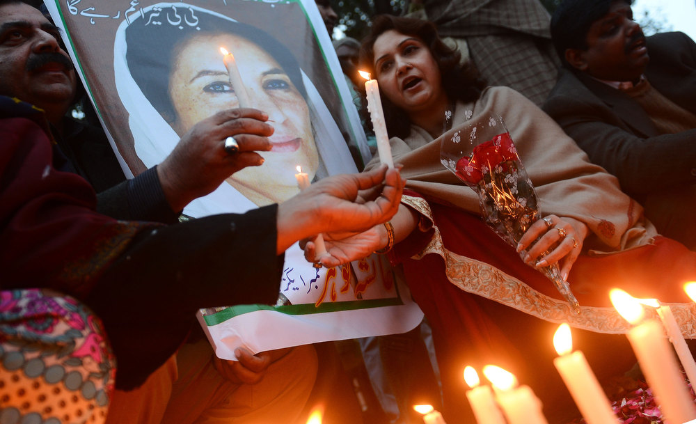 Description of . Activists of ruling Pakistan People's Party (PPP) hold a portrait of the late former Pakistan premier Benazir Bhutto during a candlelight ceremony in Lahore on December 27, 2012, on the fifth anniversary of her assassination. Vast crowds gathered to mark the fifth anniversary of the assassination of former Pakistan premier Benazir Bhutto, and to witness her son launch his own political career.  AFP PHOTO/Arif Ali/AFP/Getty Images