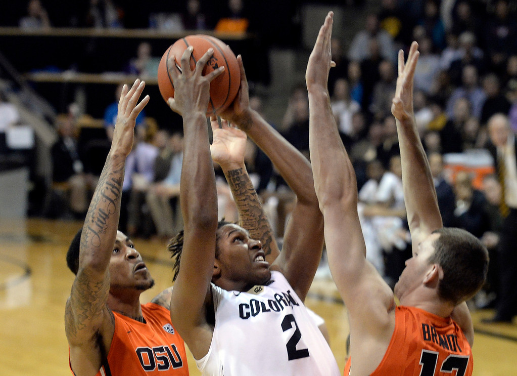 . Colorado\'s Xavier Johnson takes a shot over Eric Moreland, at left, and Angus Brandt during an NCAA game against Oregon State on Thursday, Jan. 2, at the Coors Event Center in Boulder.  Jeremy Papasso/ Camera