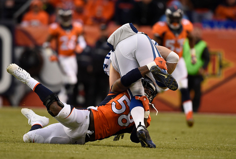 . Von Miller (58) of the Denver Broncos stops Jack Doyle (84) of the Indianapolis Colts on a gain of 4 yards in the second quarter. The Denver Broncos played the Indianapolis Colts in an AFC divisional playoff game at Sports Authority Field at Mile High in Denver on January 11, 2015. (Photo by AAron Ontiveroz/The Denver Post)