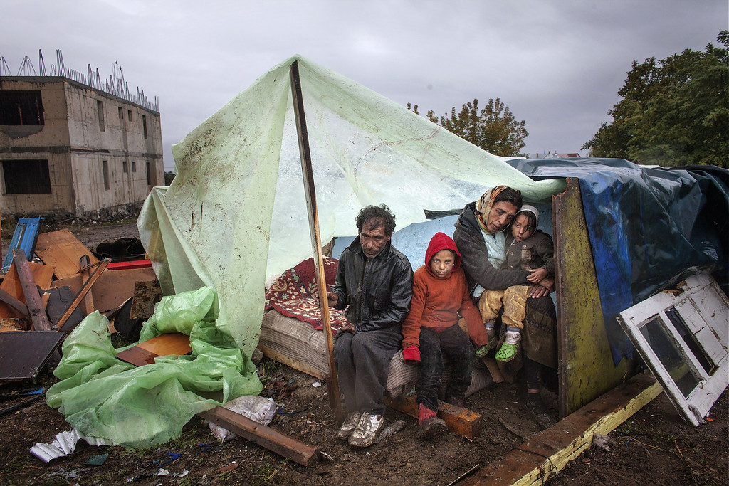 . A Roma family of Turkish origin sits under an improvised shelter during heavy rain in Eforie Sud, Romania, on September 30, 2013 before an announcement by the Mayor on their case. Romanian authorities evicted around 100 Roma from a town near the Black Sea coast without providing them with alternative housing, prompting criticism from Amnesty International. The Roma families spent three days in a nearby field despite the cold weather until the mayor decided on September 30, 2013 to host them in an old school.