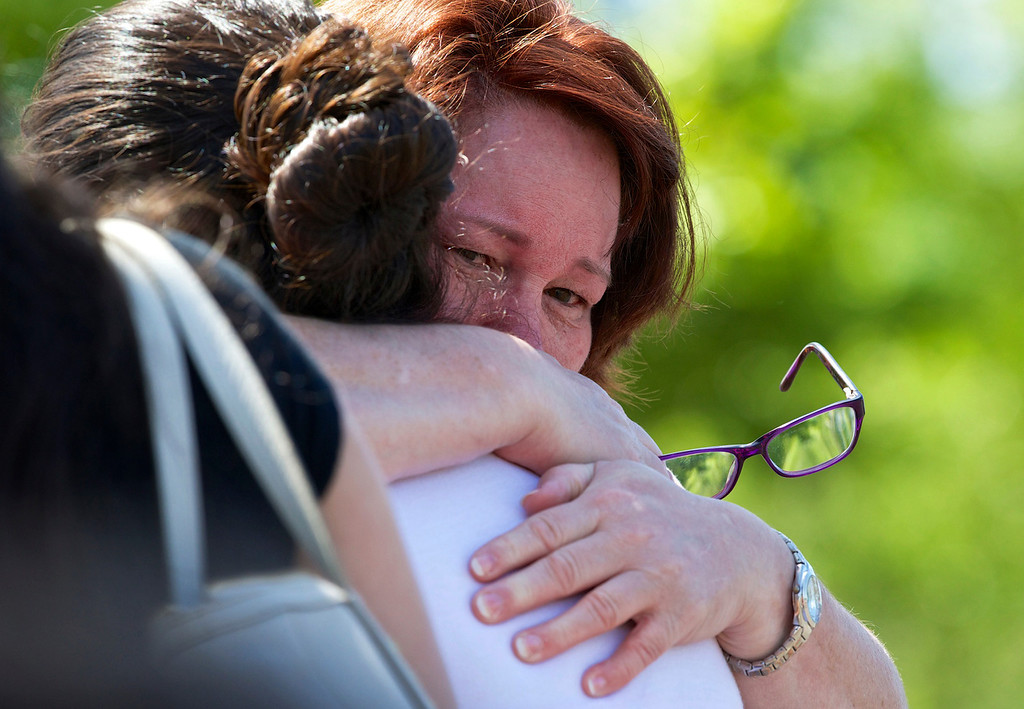 . A family embraces after students arrived at the Fred Meyer grocery store parking lot in Wood Village, Ore., after a shooting at Reynolds High School Tuesday, June 10, 2014, in nearby Troutdale. (AP Photo/The Oregonian, Thomas Boyd)