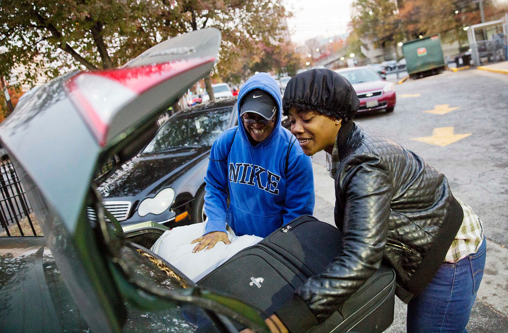 . April Traylor, of Nashville, Tenn., left, is helped by her daughter Latisha Brown to load her bags into the car after arriving on a bus to spend the Thanksgiving holiday in Atlanta, Wednesday, Nov. 23, 2016. Almost 49 million people are expected to travel 50 miles or more for the holiday, the most since 2007, according to AAA. (AP Photo/David Goldman)