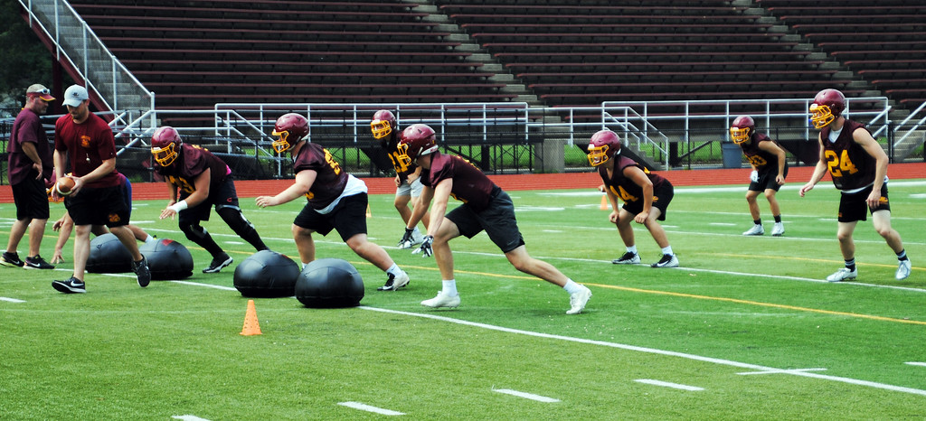 . Jon Behm - The Morning Journal<br> Avon Lake coach Matt Kostelnik runs a drill with the Shormen defense during Avon Lake\'s first day of football practice on July 30.