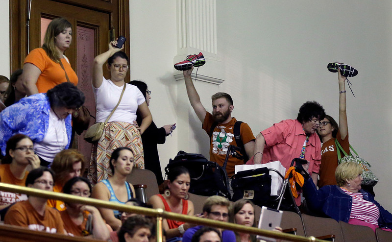 . Member of the gallery respond by holding up their shoes as Sen. Wendy Davis, D-Fort Worth, is called for a third and final violation in rules to end her filibuster attempt to kill an abortion bill, Tuesday, June 25, 2013, in Austin, Texas. The bill would ban abortion after 20 weeks of pregnancy and force many clinics that perform the procedure to upgrade their facilities and be classified as ambulatory surgical centers.  (AP Photo/Eric Gay)