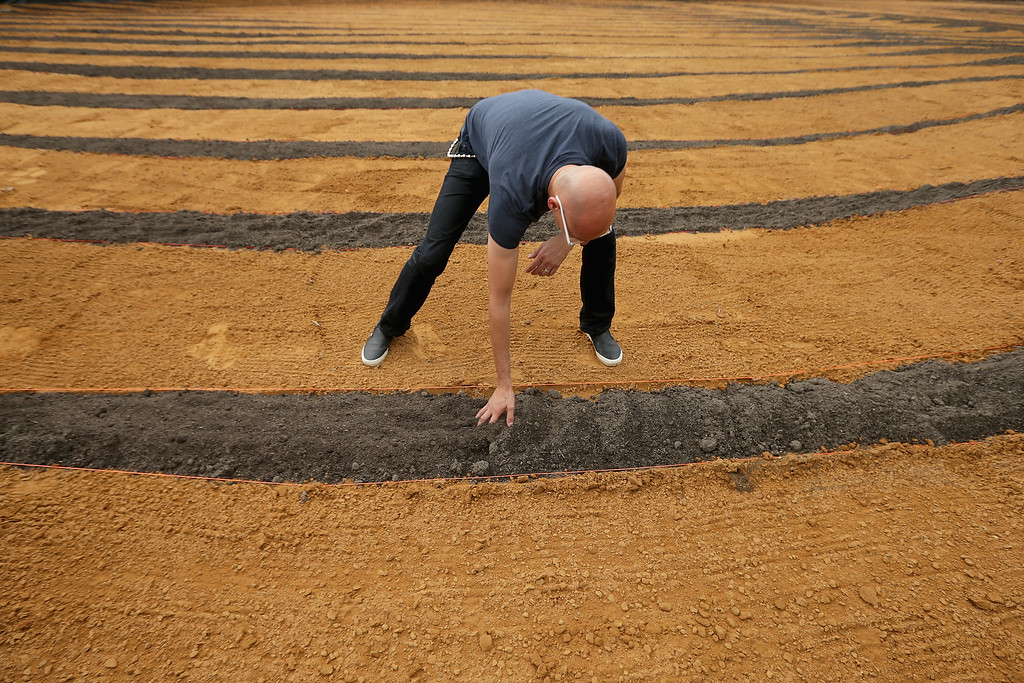 . Cuban-American artist Jorge Rodriguez-Gerada smooths dirt by hand inside his six-acre sand and soil \'facescape\' on the JFK Hockey Field along the north side of the Reflecting Pool on the National Mall October 1, 2014 in Washington, DC. (Photo by Chip Somodevilla/Getty Images)