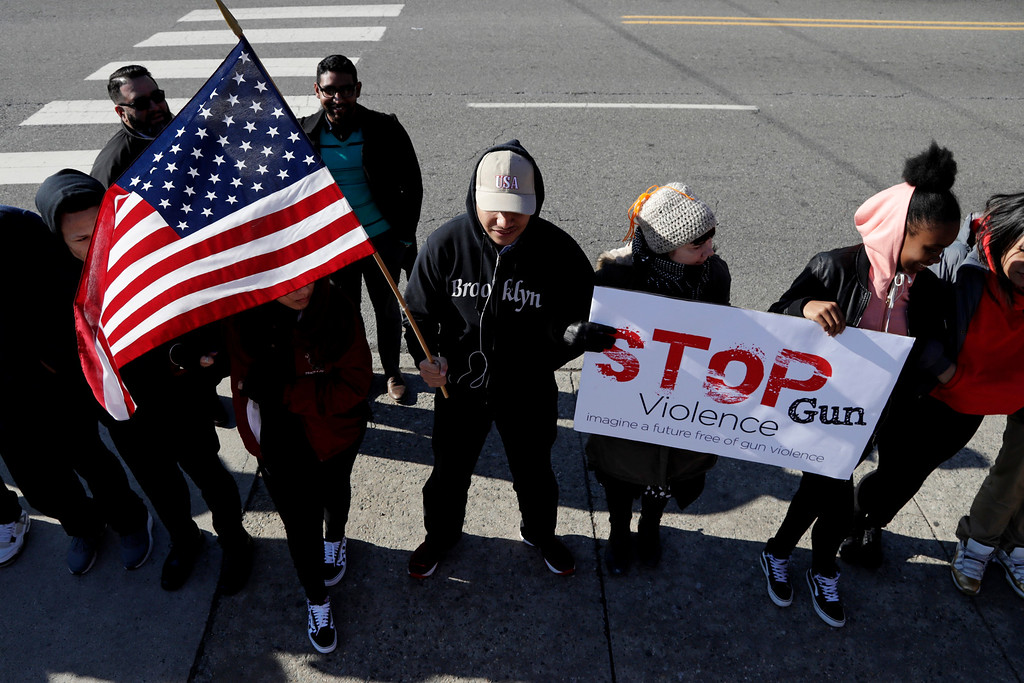. Ahmed Aboushady, center, a junior at James Ferris High School, holds a flag while standing with classmates outside of the school during a student walkout, Wednesday, March 14, 2018, in Jersey City, N.J. Students across the country planned to participate in walkouts Wednesday to protest gun violence, one month after the deadly shooting inside a high school in Parkland, Fla. (AP Photo/Julio Cortez)