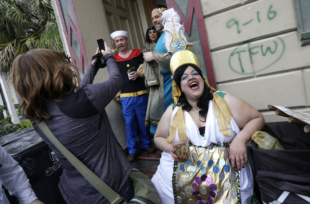 . Revelers gather for the start of the Society of Saint Anne walking parade in the Bywater section of New Orleans during Mardi Gras day, Tuesday, Feb. 12, 2013. FEMA markings from Hurricane Katrina are still displayed on the wall. (AP Photo/Gerald Herbert)