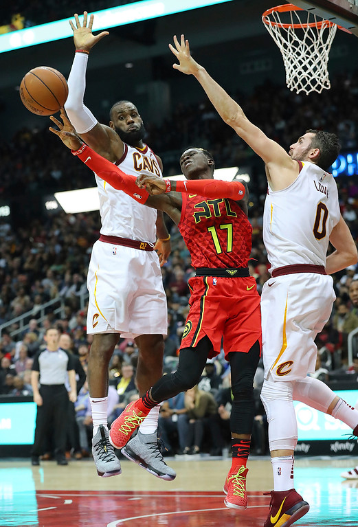 . Atlanta Hawks guard Dennis Schroder passes off under the basket on a double team by Cleveland Cavaliers LeBron James and Kevin Love during the first half of an NBA basketball game, Thursday, Nov. 30, 2017, in Atlanta. (Curtis Compton/Atlanta Journal-Constitution via AP)