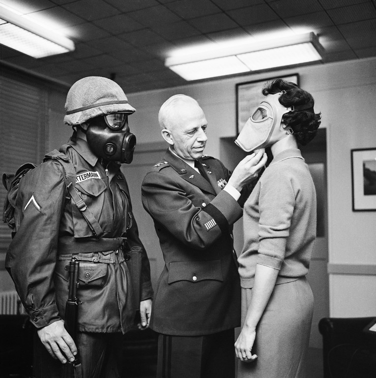 . Maj. Gen. Marshall Stubbs, Army?s chief chemical officer, checks new civilian gas mask being worn in his Pentagon office by secretary, Margaret Francis, Jan. 19, 1959.  Pfc. Warner Bitterman, left, New Salem, N.D., wears army?s latest type. Masks are same except in appearance. Defense officials say over 32,000 of these are in use for training purposes but none is available for civilian purchase. (AP Photo)