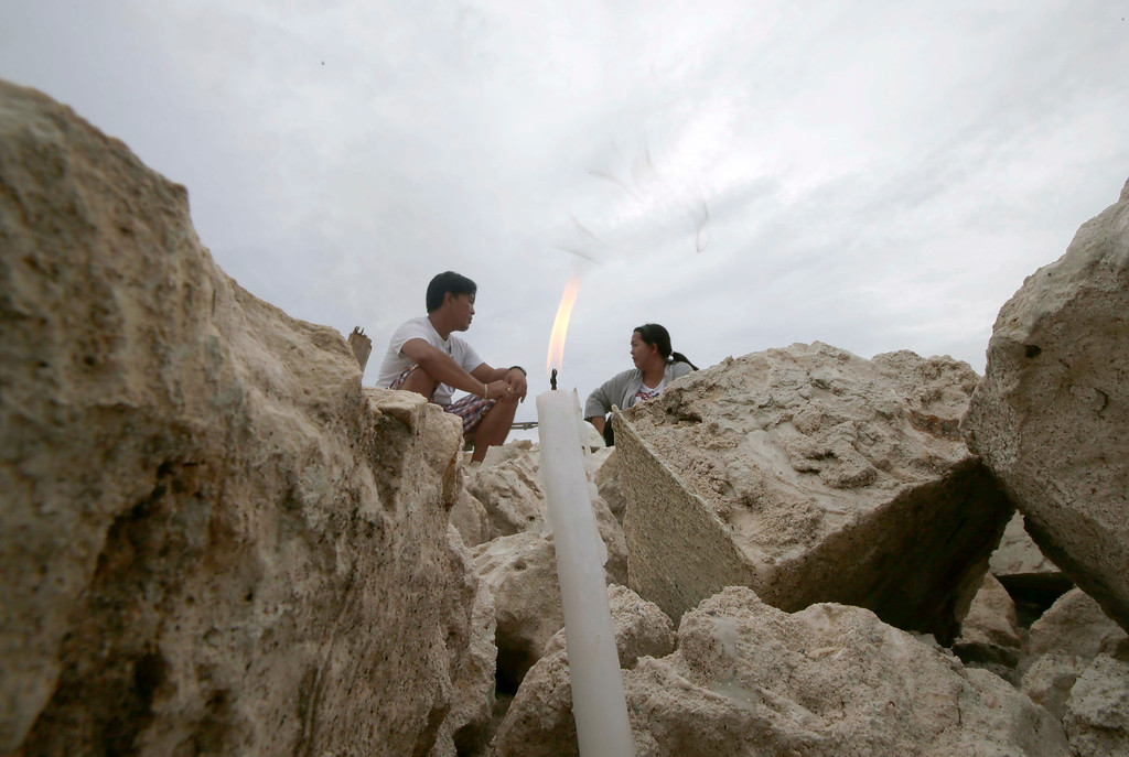 . Hannah Jumang-it and her brother Mark Dave Mejorada sit by the ruins of Our Lady of Light church as they look for their missing father Necitas Mejorada, a lay minister, in Loon township, Bohol province in central Philippines Thursday, Oct. 17, 2013.   (AP Photo/Bullit Marquez)