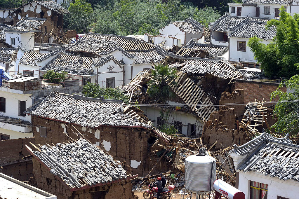 . A man rides a motorbike through a narrow road surrounded by damaged houses in Longtoushan township of Ludian county in Zhaotong, southwest China\'s Yunnan province on August 5, 2014. More than 367 people died and nearly 2,000 were injured when a strong earthquake hit southwest China\'s mountainous Yunnan province, bringing homes crashing to the ground and sparking a massive relief operation. AFP PHOTO   STR/AFP/Getty Images