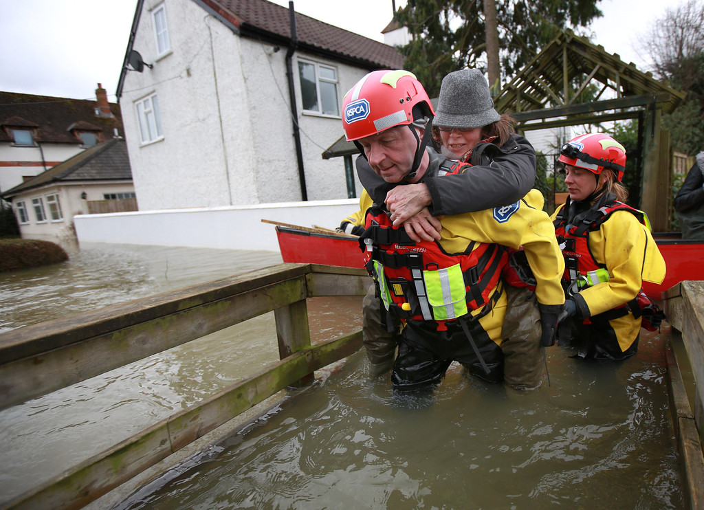 . Tricia Tompkins receives a lift from a member of the RSPCA water rescue team as they evacuate her pet cats on February 12, 2014 in Wraysbury, England.The Environment Agency contiues to issue severe flood warnings for a number of areas on the river Thames in the commuter belt west of London. With heavier rains forecast for the coming week people are preparing for for the water levels to rise.  (Photo by Peter Macdiarmid/Getty Images)