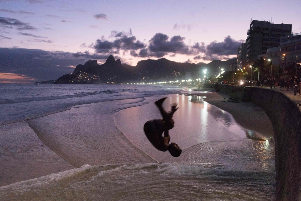 . A young man jumps from a wall on the beach of Arpoador, neighbouring the famous Ipanema beach (background), on May 14, 2016 as the sun sets in Rio de Janeiro. FRANCOIS XAVIER MARIT/AFP/Getty Images