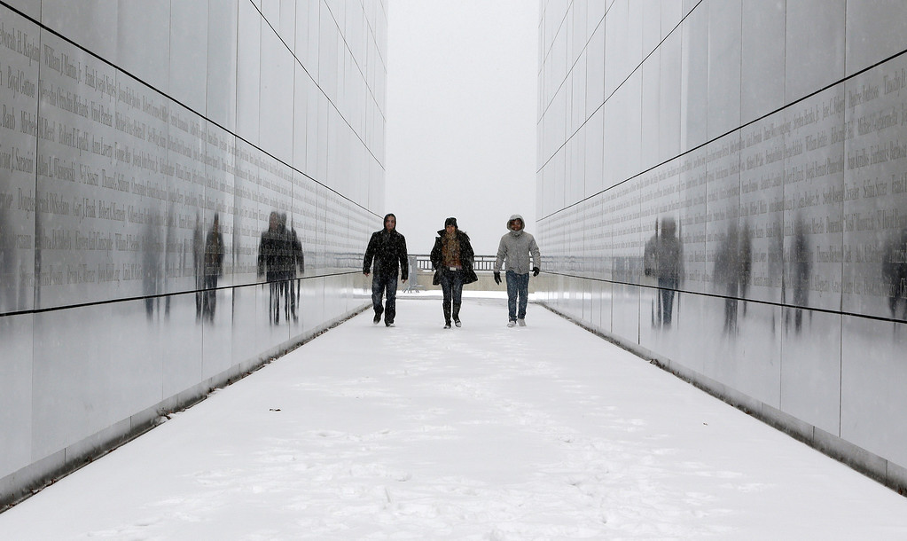 . Manuel Archila, from left, Vera Martinez and Jose de la Hoz, who are on vacation from their native Colombia, walk on snow covered ground through the Empty Sky Memorial at Liberty State Park, Tuesday, Jan. 21, 2014, in Jersey City, N.J. (AP Photo/Julio Cortez)