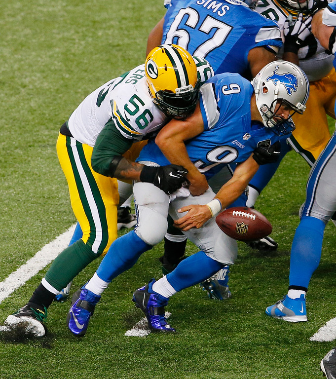 . Green Bay Packers outside linebacker Julius Peppers (56) forces Detroit Lions quarterback Matthew Stafford (9) to fumble during the second half of an NFL football game in Detroit, Sunday, Sept. 21, 2014. (AP Photo/Paul Sancya)
