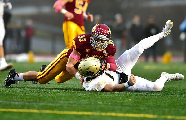 12/14/2019 Mike Orazzi | Staff St. Joseph High School's Michael Morrissey (33) pressures Daniel Hand's Phoenix Billings (17) causing an interception at Veteran's Stadium in New Britain on Saturday.