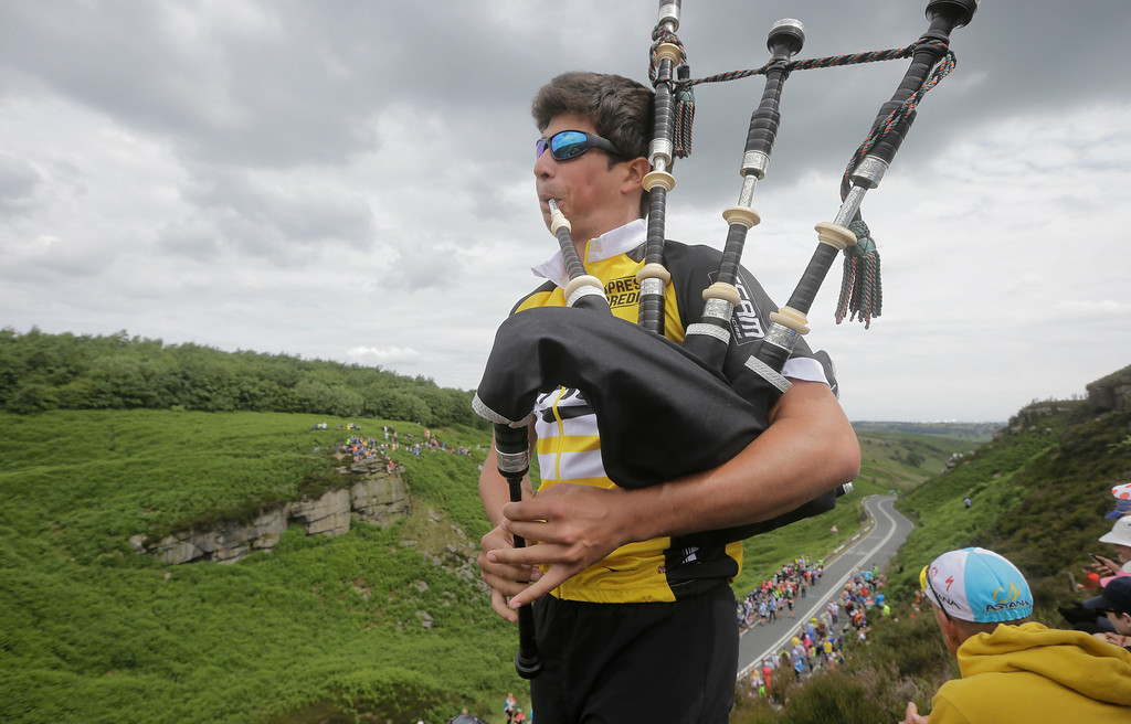 . A bag piper plays as spectators wait for the pack to pass during the second stage of the Tour de France cycling race over 201 kilometers (124.9 miles) with start in York and finish in Sheffield, England, Sunday, July 6, 2014. (AP Photo/Laurent Cipriani)