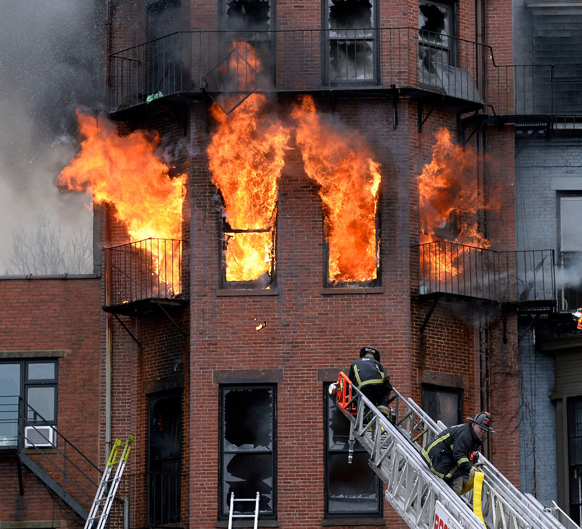 . Boston firefighters work a multi-alarm brownstone fire, Wednesday, March 26, 2014, in Boston. A Boston city councilor said two firefighters have died in a fire that ripped through the brownstone. (AP Photo/The Boston Herald, Christopher Evans)