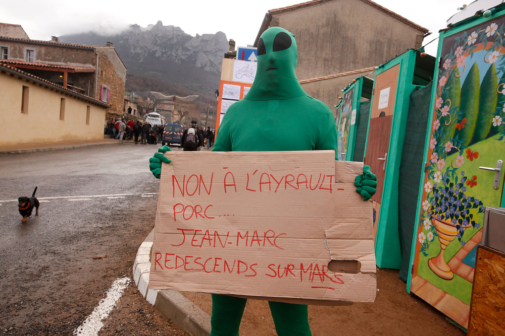 Description of . A man dressed as an alien holds up a sign after the time passed 11.11 am, the time the Mayan Apocalypse was supposed to occur in Bugarach village on December 21, 2012 in Bugarach, France. The prophecy of an ancient Mayan calendar claimed that today would see the end of the world, and that Burgarach is the only place on Earth which will be saved from the apocalypse. (Photo by Patrick Aventurier/Getty Images)