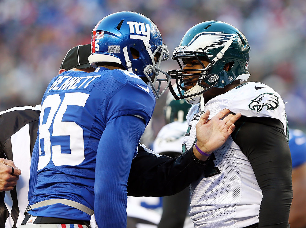 Description of . Brandon Graham #54 of the Philadelphia Eagles and  Martellus Bennett #85 of the New York Giants argue after a play in the fourth quarter at MetLife Stadium on December 30, 2012 in East Rutherford, New Jersey. The New York Giants defeated the Philadelphia Eagles 42-7.  (Photo by Elsa/Getty Images)