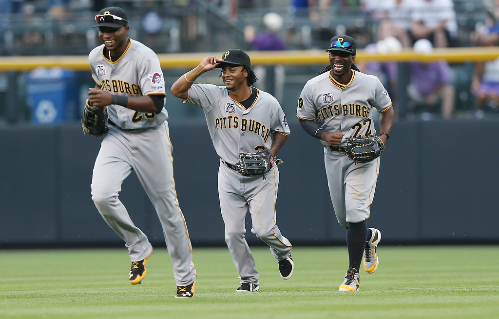 . Pittsburgh Pirates outfielders Gregory Polanco, left, Michael Martinez and Andrew McCutchen, right, miles after the Pirates\' 7-5 victory over the Colorado Rockies in a baseball game in Denver on Sunday, July 27, 2014. (AP Photo/David Zalubowski)