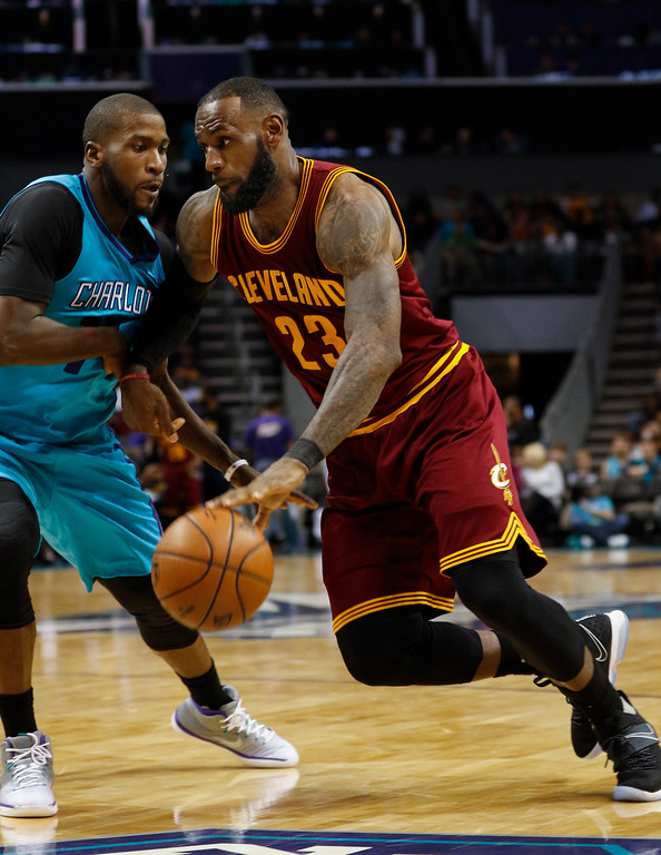 . Cleveland Cavaliers forward LeBron James, right, drives into Charlotte Hornets forward Michael Kidd-Gilchrist in the second half of an NBA basketball game in Charlotte, N.C., Saturday, Dec. 31, 2016. Cleveland won 121-109. (AP Photo/Nell Redmond)