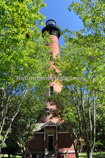 """Currituck Beach Lighthouse <br /> On December 1, 1875 the beacon of the Currituck Beach Lighthouse filled the remaining """"dark space"""" on the North Carolina coast between the Cape Henry light to the north and Bodie Island to the south. To distinguish the Currituck Beach Lighthouse from other regional lighthouses, its exterior was left unpainted and gives today's visitor a sense of the multitude of bricks used to form the structure. The lighthouse was automated in 1939 when the United States Coast Guard assumed the duties of the Bureau of Lighthouses. At a height of 158 feet, the night beacon still flashes at 20-second intervals to warn ships hugging the chain of barrier islands along the coast."""