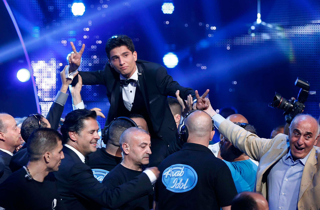 ". Palestinian singer Mohammed Assaf reacts after being announced winner of the Season 2 finale of ""Arab Idol\"" in Zouk Mosbeh area, north of Beirut June 22, 2013. REUTERS/Mohammed Azakir"