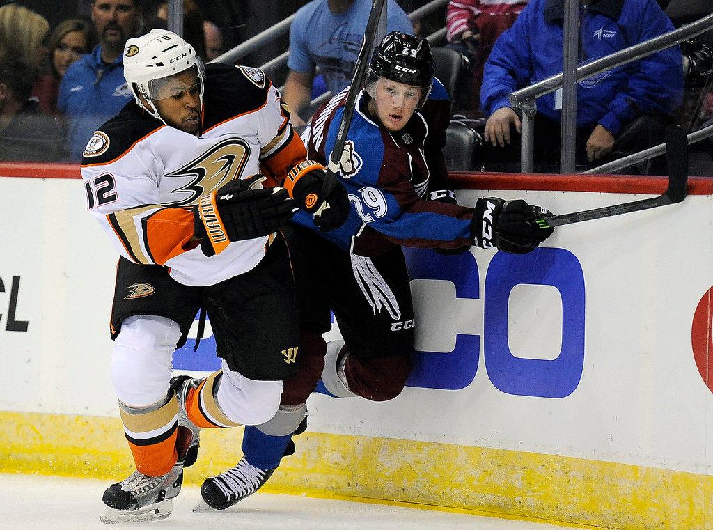 . Anaheim Ducks right wing Devante Smith-Pelly, left, and Colorado Avalanche center Nathan MacKinnon, right, fight for the puck in the first period of an NHL preseason hockey game Monday, Sept. 22, 2014 in Denver. (AP Photo/Chris Schneider)