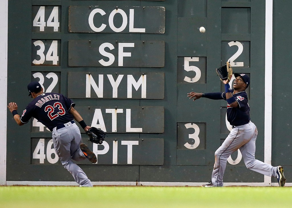 . Cleveland Indians\' Michael Brantley (23) veers off as Greg Allen, right, makes the catch on the fly out by Boston Red Sox\'s Mitch Moreland during the fifth inning of a baseball game in Boston, Tuesday, Aug. 21, 2018. (AP Photo/Michael Dwyer)