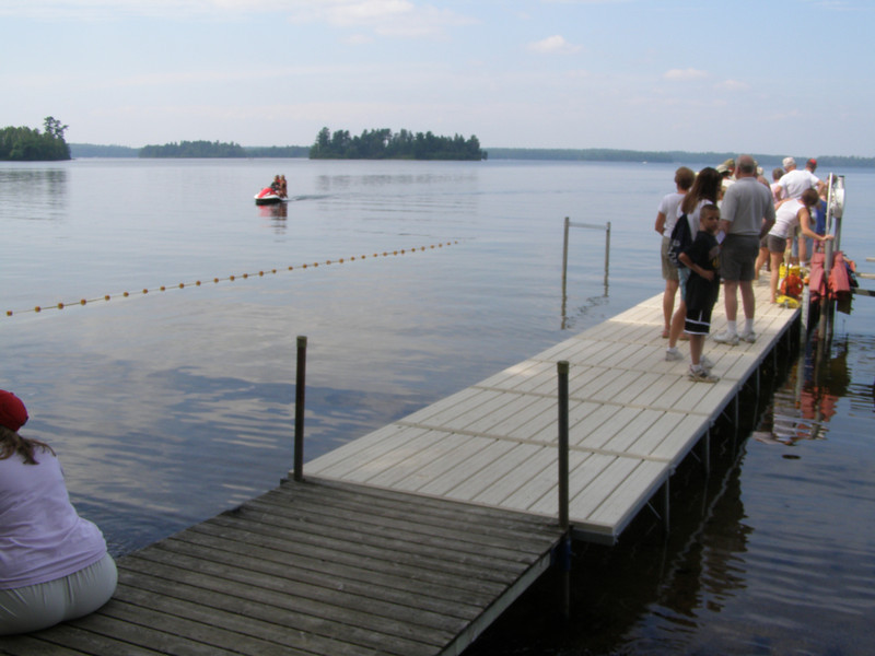 "Visitors wait for the next pontoon boat ""research"" excursion out onto the lake while new visitors show up via Jetski."