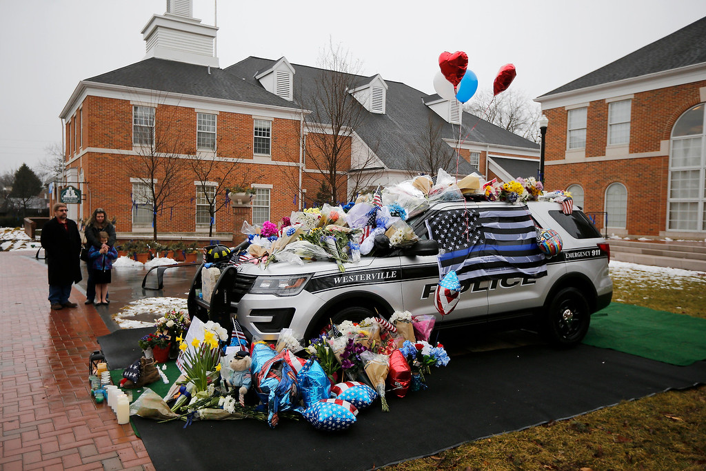 . Mourners gather and leave flowers on a police cruiser parked in front of City Hall in Westerville, Ohio, on Sunday, Feb. 11, 2018. Westerville police officers Anthony Morelli and Eric Joering were killed in the line of duty Saturday when a suspect opened fire on them as they responded to a call at a residence.  (/The Cincinnati Enquirer via AP)