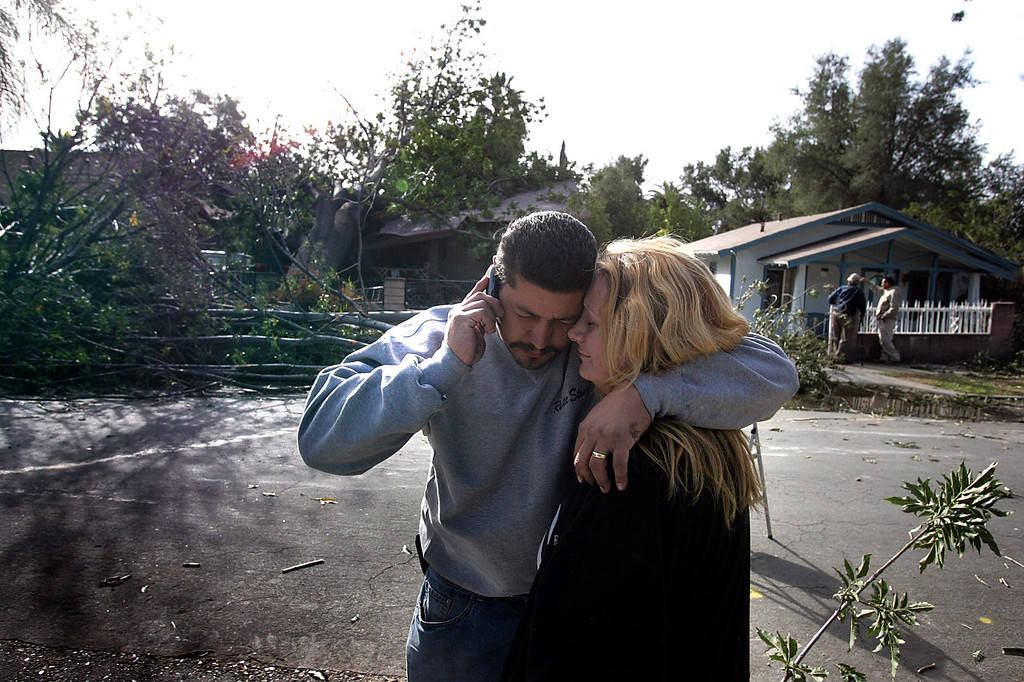 . Carlos and Heather Flores stand before their home at 100 Cedar Street in Pasadena after a city tree crashed into their home trapping them and their three kids Thursday, December 1, 2011 as winds gusting up to 80 miles an hour whipped through the west San Gabriel Valley overnight. As many as 230,000 were reported without power and the city of Pasadena declared a state of emergency. The Flores family was helped by neighbors and their home was red tagged. (SGVN/Staff Photo by Sarah Reingewirtz/SXCITY)